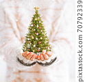 Cute woman holds decorated christmas tree in her hands. Merry Christmas and a Happy new year concept 70792339
