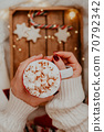 Close up of women's hands holding white mug with hot cocoa, tea or coffee and marshmallow. 70792342