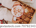 Close up of women's hands holding white mug with hot cocoa, tea or coffee and marshmallow. 70792343