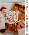 Close up of women's hands holding white mug with hot cocoa, tea or coffee and marshmallow. 70792344