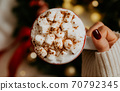 Close up of women's hands holding white mug with hot cocoa, tea or coffee and marshmallow. 70792345
