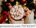 Close up of women's hands holding white mug with hot cocoa, tea or coffee and marshmallow. 70792347