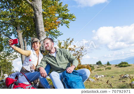 Young couple drinking water while resting on the rock during the travel in the mountains 70792971