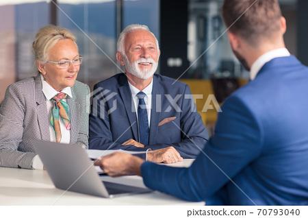 Positive aged couple consulting with insurance agent 70793040
