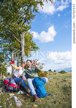 Cheerful young couple taking a selfie outdoor during the travel in the mountains 70793547
