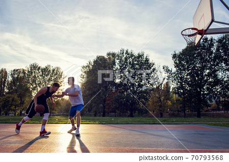 Two street basketball players playing hard on the court 70793568