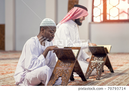 Two religious muslim man praying together inside the mosque 70793714