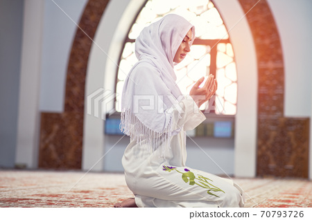 Young muslim woman reading Quran in the mosque and sunlight falling from the window 70793726