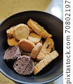 Round crackers made of white and rye bread on a dark-colored plate 70802197