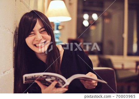 A woman reading a magazine at a cafe and laughing 70803965