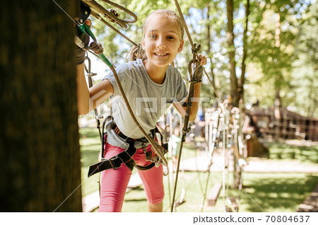 Smiling girl climbs in rope park, playground 70804637