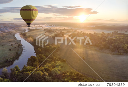 Hot air balloon over river on sunset 70804889