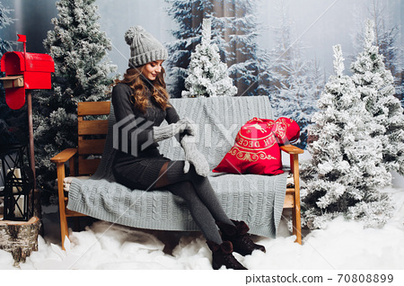 Woman in gray sitting on bench among christmas 70808899