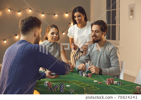 Group of young friends awaiting for card from deck during betting and playing poker 70824241