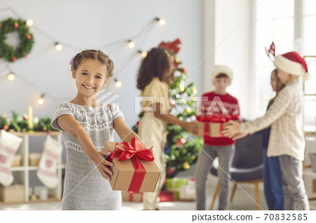 Cute little smiling girl holds out a Christmas present on a blurred background of her friends. 70832585