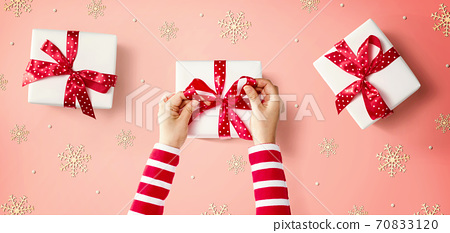 Person making Christmas gift boxes 70833120