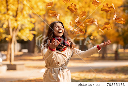 Joyful young woman in autumn outfit catching yellow leaves during her walk at park on bright fall day 70833178