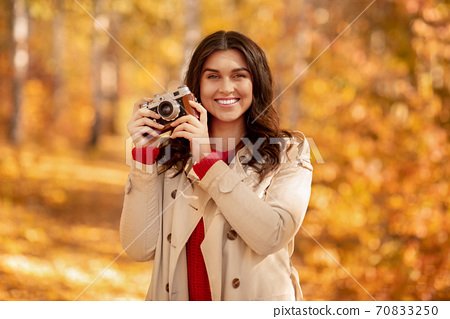 Portrait of lovely female photographer with retro camera posing and smiling at yellow autumn park 70833250