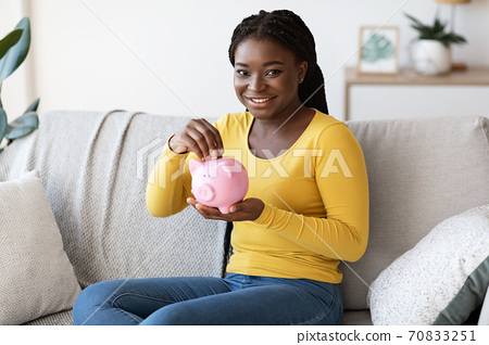 Happy African American Woman Holding Piggy Bank, Sitting On Couch At Home 70833251