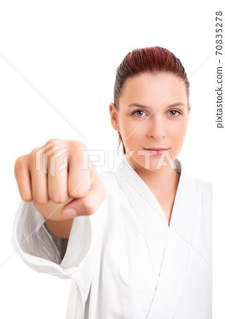 Girl in white martial arts kimono punching the camera 70835278