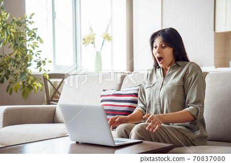 Amazed indian woman lottery winner look at laptop at home excited by online win. 70837080