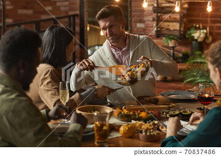 Man Serving Food at Dinner Party 70837486