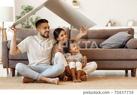 Happy multiethnic family under fake roof in living room. 70837738