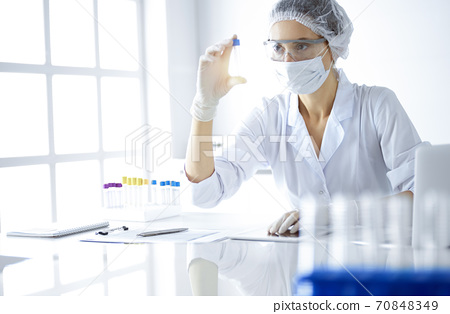Professional female scientist in protective eyeglasses researching tube with reagents in sunny laboratory. Medicine and science researching 70848349