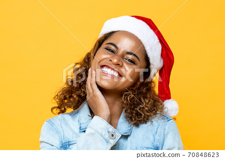 Surprised happy African American woman wearing Christmas hat smiling  70848623