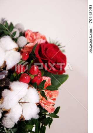 Bouquet with red roses, cotton balls, cones, spruce and other flowers. Circle flowers bunch. Close up 70848993