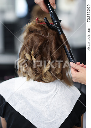 Woman in beauty salon is twisted curls of hair on curling iron. 70851290