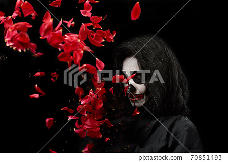 woman with a make-up skeleton stands in black clothes and a transparent hood 70851493