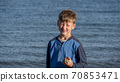 Portrait of a child against the sea. The boy holds the candy in his hands. 70853471