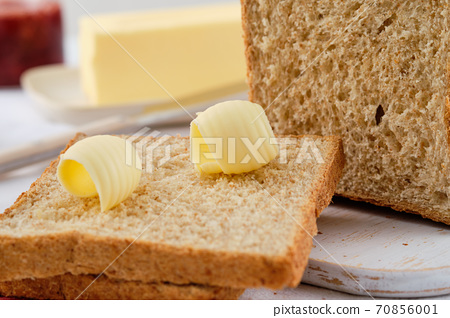 Butter curl on toast bread. Healthy breakfast with bran bread toast, butter and jam. 70856001
