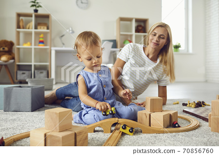 Young babysitter and little child playing with wooden blocks in cozy nursery room 70856760
