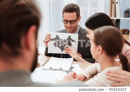 Adult psychologist shows cards with Rorschach. 70858307