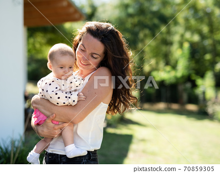 Woman holding baby daughter outdoors in backyard. Copy space. 70859305