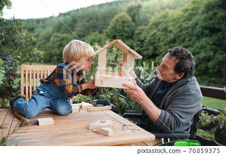 Small boy with senior grandfather in wheelchair constructing birdhouse, diy project. 70859375