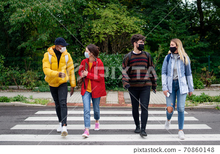 Group of young people crossing road outdoors in town, talking. Coronavirus concept. 70860148