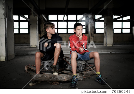 Group of teenagers boys indoors in abandoned building, smoking cigarettes. 70860245