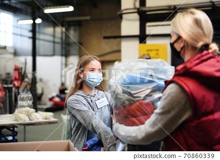 Woman donating clothes community charity donations center, coronavirus concept. 70860339