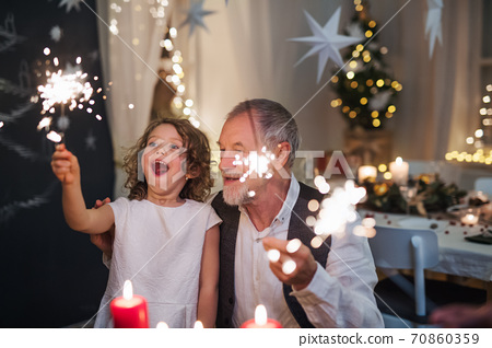 Senior grandfather with small granddaughter indoors at Christmas, sitting at table with sparklers. 70860359