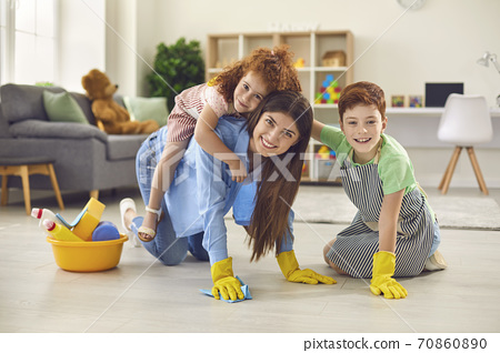 Happy mother with her children cleaning floor at apartment. Parent with kids having fun while doing domestic chores 70860890