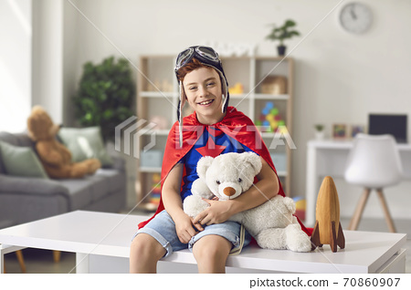 Boy in superhero costume sitting on table at home with toy and smiling 70860907