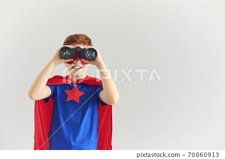 Smiling boy playing role of superhero at home with binoculars and looking at camera, copy space 70860913