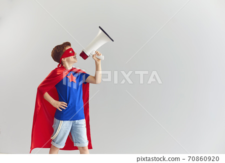 Smiling boy playing role of superhero at home with speaker in hand, copy space 70860920