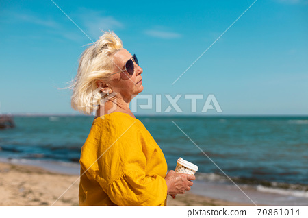 An adult woman in sunglasses and a yellow blouse with a paper cup of coffee to go by the sea on a sunny day. Coffee to go 70861014