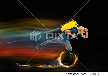 Fast delivery service - deliveryman on unicycle driving with order in fire on dark background 70861976