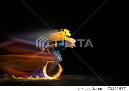 Fast delivery service - deliveryman on unicycle driving with order in fire on dark background 70861977