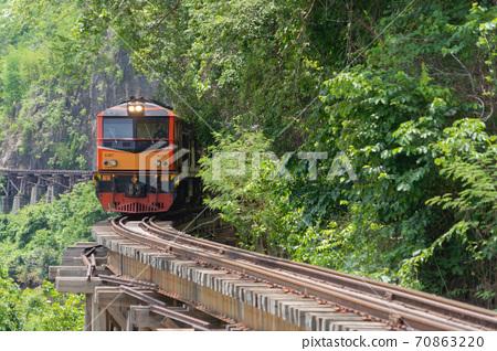 Thai local old classic train on railway on River Kwai Bridge in Kanchanaburi town, Thailand in public transportation concept. 70863220